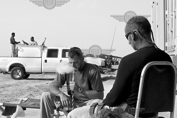 Private security operators Mark Hammond (left) and John Fox from the British company ArmorGroup smoke a water pipe and relax in Al Asad air base in north western Iraq on November 2, 2006. The coalition forces and civilian administration in Iraq depend heavily on the controversial presence of thousands of private security personnel in their reconstruction efforts and military operations.