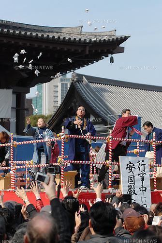 People try to catch thrown roasted soy beans and snacks at Tokyofs Zojoji temple as part of the Setsubun festival which marks the lunar calendar start of spring. The beans are supposed to drive away the evil spirits that bring misfortune and bad health with them.