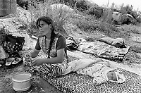Albania. Province of Fier. Fier. A gypsie mother and her sleeping daughter sit on a foam matress on the ground. A  group of destroyed bunkers  are left over in an illegal rubbish dump. Enver Hoxha (1908-1985) was for 40 years a dictator and a communist leader. He decided after the historic break with Russia in 1961 to protect his country from any invaders by investing in a massive fortification (more than a million bunkers were built over the years till 1985). © 2003 Didier Ruef