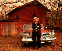 Portrait of older man with cowboy hat on leaning on a Plymouth in front of a red barn. Elderly. Alabama USA.