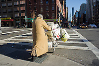 Woman with her possessions on a shopping cart crosses Seventh Avenue in the Chelsea neighborhood of New York on Saturday, December 24, 2011.  (© Richard B. Levine)