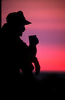 The profile silhouette of a man drinking a mug of coffee and watching the sun rise.