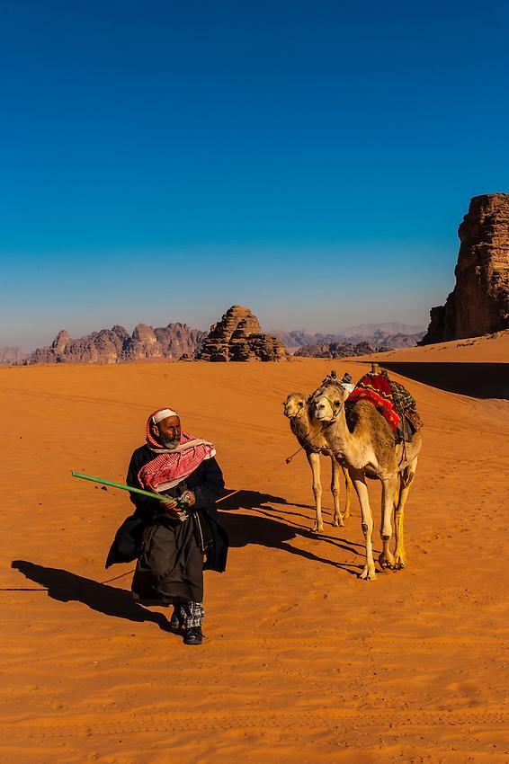 Bedouin man in the Arabian Desert with his camels, Wadi Rum, Jordan.