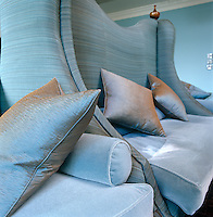 A detail highlighting the various textures such as the silk scatter cushions and velvet seats of a duck-egg blue banquette designed by Martin Hulbert