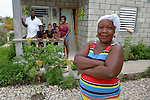 """Reseha Rosier stands in front of her house in a model resettlement village constructed by the Lutheran World Federation in Gressier, Haiti. The settlement houses 150 families who were left homeless by the 2010 earthquake, and represents an intentional effort to """"build back better,"""" creating a sustainable and democratic community. Behind Rosier are her daughter and her family, who live with the woman."""