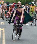 Wearing only a cape, boots and golden pants, a colorful painted bicycle rider peddles down the street at the 21st Annual Fremont Summer Solstice Parade in Seattle on June 20, 2009. The parade was held Saturday, bringing out painted and naked bicyclists, bands, belly dancers and floats. (Jim Bryant Photo © 2009)