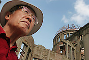 Yasuhiko Shigemoto, Japanese haiku poet, standing beside the A-Bomb Dome,  which survived the August 6th 1945 atomic bombing of Hiroshima. The dome, now a memorial, has been an inspiration for Mr. Shigemoto's poems, Hiroshima, Japan. 30.07.05