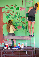 Volunteers paint a wall at the Costa Rica Wildlife Sanctuary run by Vanessa Lizano and her family. Moin, Limon, Costa Rica.
