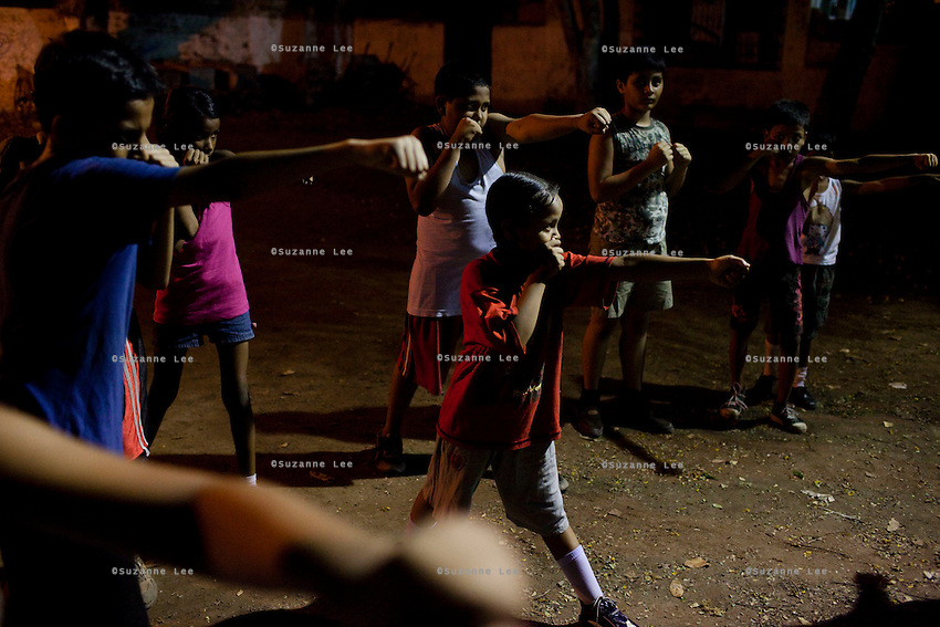 Razia Shabnam (unseen) conducts a training session in Biyam Samiti park with children from the area of Kidderpore, Calcutta, West Bengal, India. Razia Shabnam, 28, was one of the first women boxers in Kolkata. She was also the first woman in her community to go to college. She is now a coach and one of only three international female boxing referees in India.  Photo by Suzanne Lee for Panos London