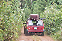 A Jeep with a canoe on top travels the rough road into Craig Lake State Park near Michigamme Michigan.