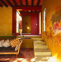 A mural has been painted on the rustic walls of the living area in this guesthouse