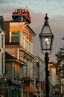 USA, Newport, RI - Colonial gas light in soft focus with view down Thames street to the Brick Alley pub with an old Fire Engine on the roof.