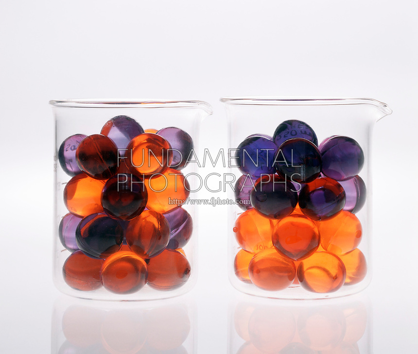 ENTROPY: ILLUSTRATION<br /> (Variations Available)<br /> Arrangement of Beads in 2 Beakers<br /> Two beakers contain orange &amp; purple beads.  Because entropy can be viewed as a measure of disorder, the arrangement in which the colors are separated represents a system of lower entropy than the one in which the colors are mixed.