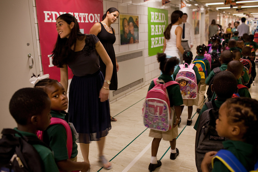 Liza Dubovsky, left, with Principal Gina Ribiero, center, teach the kindergarteners to walk in a line between classrooms on the first day of class at Brownsville Elementary School in Brooklyn, NY on August 15, 2011.