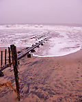 The remaining storm swell washes ashore onto the dirty beach after a major Nor'easter at Rehoboth Beach, Delaware, USA.