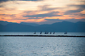 The UVM Sailing Team practices at sunset on Lake Champlain.