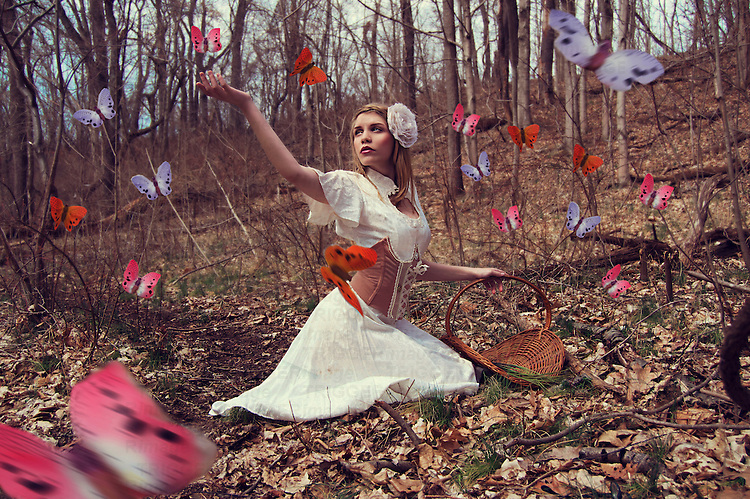Photograph of a young caucasian woman with blonde hair wearing a lacy white flower on the side of her head. She is sitting in a wooded area that looks like it is still clinging to winter's chill in the season of the Imbolc. She is wearing a white vintage dress with a tan colored corset and holding a brown basket in her left hand. She is reaching out to colorful butterflies with her right hand which are flying all around her.