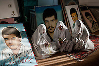 The mother of Martyrs, those who died in the Iran-Iraq war, praying at the graves of their sons and surrounded by their portraits.