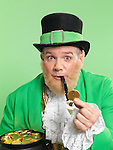 Leprechaun in bright green clothes holding a golden coin in his hand