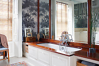 A mahogany bath surround and mirrors and 'Psyche Au Bain' panoramic black and white wallpaper by Zuber add a luxurious touch to a bathroom. A mirror placed on the wall behind the bath gives the room a sense of space.