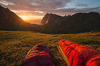 Watching colorful summer sunset over Bunes beach from sleeping bags, Moskenesøy, Lofoten Islands, Norway