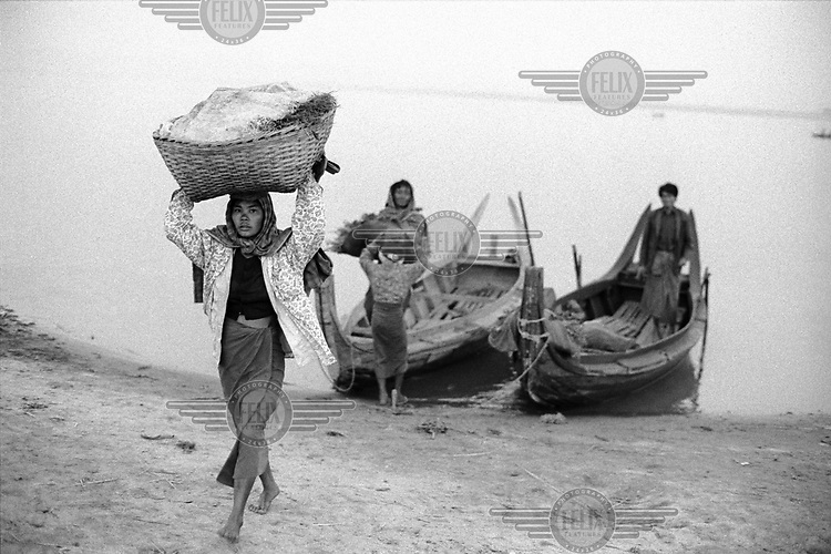 Unloading produce from boats on the way to the market, having crossed the Ayeyarwady (Irrawaddy) River.