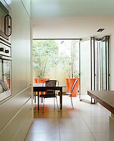 In the kitchen/dining area of a contemporary London house a series of sliding glass doors open onto the garden beyond