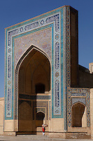 Low angle view of the gateway to the Kalyan mosque, 15th-16th century, Bukhara, Uzbekistan, pictured on July 7, 2010, in the early morning light. A woman with an umbrella, walking through the gate, is dwarfed by the immense size of the elaborately tiled archway. Bukhara, a city on the Silk Route is about 2500 years old. Its long history is displayed both through the impressive monuments and the overall town planning and architecture.