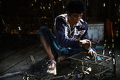 33 year old Way Lut is a crab fisherman, here he fixes his crab nets in their hut in Damin Naung village in Pyapon district of Myanmar.