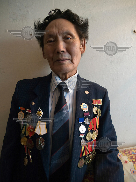 A Yakutian war veteran proudly posing with his medals and decorations..