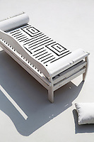 A contemporary rustic bench on the roof terrace is upholstered in a white canvas with a rough brush stroke design