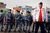 "A man in ""Russia"" jacket stands in front of riot police guarding a demonstration by Communist supporters on Labour Day. © Justin Jin"