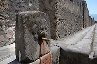 Fountain, Vico Dei Vettii, Pompeii, with its spout still in place. One of 42 public fountains fed by lead piping from water towers around the city