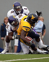 East Carolina defensive end C.J. Wilson (95) and safety Van Eskridge (4) tackle WVU running back Noel Devine. The WVU Mountaineers defeated the East Carolina Pirates 35-20 at Mountaineer Field at Milan Puskar Stadium, Morgantown, West Virginia on September 12, 2009.