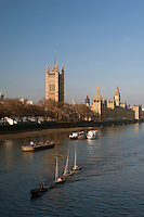 Sail boats are towed down the River Thames, past the Houses of Parliament and Big Ben, London, UK
