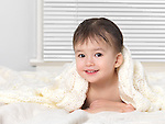 Cute smiling two year old baby boy peeking out from under a blanket after taking a bath