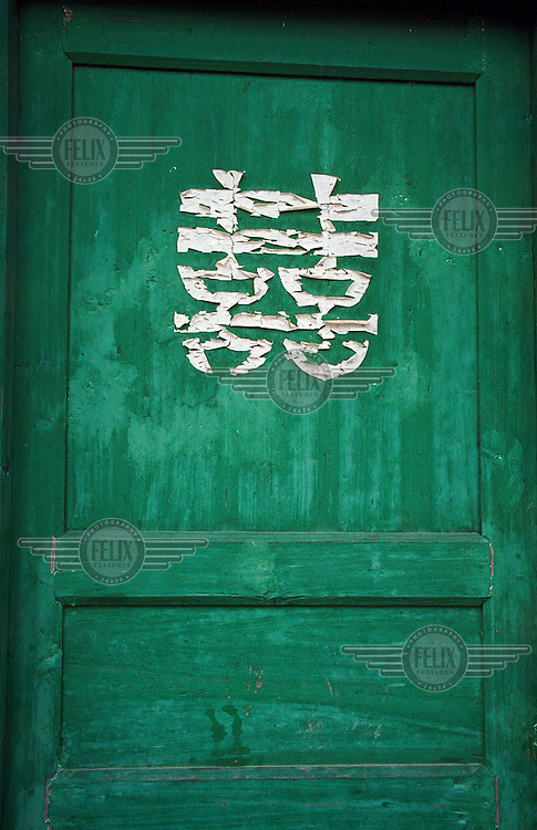 A faded double happiness character remains pasted on a door in a village near Quanzhou.