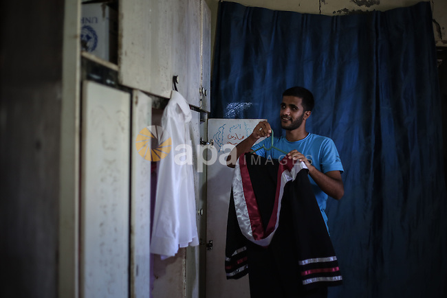 Fadi al-Shami, 21, a Palestinian blind youth, wears his graduation suit at his family home in Central Gaza Strip on Aug 17, 2013. al-Shami lost his sight after he was injured by an Israeli airstrike next to his family home at al-Musaddar village in central Gaza Strip during the Gaza–Israel conflict in 2006. Photo by Mahmoud Hamda