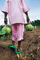 Rwanda. Southern province. District of Muhanga. Central jail of Gitarama. A black teenager boy, wearing the pink prisoner's clothes, walks outside of the prison and is returning to the minors block. He has picked up two cabbages during the morning agriculture's lesson. Minors in detention. Detention pending trial and after trial, when sentenced to prison. The non-governmental organization (NGO) Fondation DiDé - Dignité en détention runs the Encademi (Encadrement des mineurs) program. Prison centrale de Gitarama. Quartier des mineurs.  © 2007 Didier Ruef