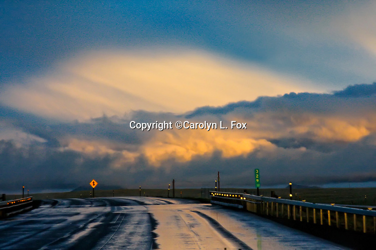Storm clouds and rain loom over the Kansas landscape, making the highway wet and slick.