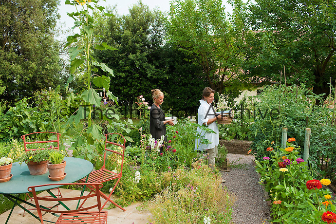 Guests carrying plates and baskets through the vegetable garden for an al fresco dinner