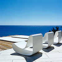 Three designer chairs on a terrace with a magnificent view of the sea