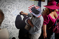 "Phoenix, Arizona, March 27, 2010 - Supporters sign a traveling board during the third rally of the 20-day Tea Party Express tour form a Tea Party bus window at the Arizona capital. The board, which was created by Bob Root, is being signed by supporters all along the tour, including Sarah Palin (in blue) which says, ""God Bless us all, Thank You, Sarah."" The tour which began in Searchlight, NV, hometown of Senate Majority Leader Harry Reid, will wind through the United States ending up in Washington, D.C. on April 15 for a tax day rally. ."