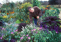 Garden writer Graham Rice in his garden of vegetables and flowers, smiling man working in annuals garden