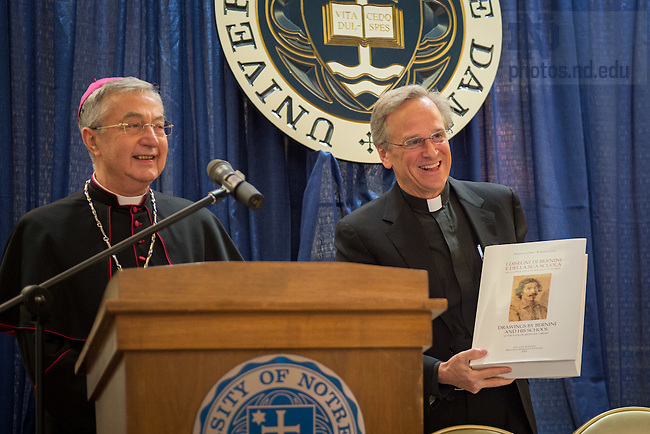 """May 9, 2016; Archbishop Jean-Louis Brugues, Archivist and Librarian of the Holy Roman Church, presents University of Notre Dame President Rev. John I. Jenkins, C.S.C. with a gift at a ceremony where Archbishop Brugues and Fr. Jenkins signed a memorandum of understanding for collaboration and exchanges between the Vatican Library and Notre Dame.  The signing ceremony was in conjunction with the conference """"The Promise of the Vatican Library,"""" an international academic conference highlighting the holdings of the Vatican Library and opportunities for future research.(Photo by Matt Cashore/University of Notre Dame)"""