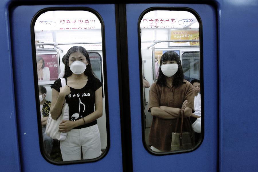 Masked Chinese women travel on the Beijing subway June 13, 2003. Beijing, the most infected city in the world, has reported no new SARS on six of the past eight days.  It reported one more from the disease in the 24 hours to 10 a.m. on Wednesday, but the Health Ministry said there were none elsewhere in China and no new deaths. ..However, the WHO has expressed concern about China's failure to record how about half its patients caught the potentially deadly respiratory illness and to diagnose properly some milder cases of Severe Acute Respiratory Syndrome. ..
