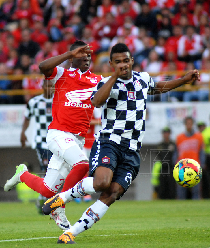 BOGOTA - COLOMBIA -22 -03-2014: Jefferson Cuero (Izq.) jugador de Independiente Santa Fe disputa el balón con Edwin Avila (Der.) jugador de Boyaca Chico FC, durante partido por la fecha 12 de la Liga Postobon I-2014, jugado en el estadio Nemesio Camacho El Campin de la ciudad de Bogota. / Jefferson Cuero (L) player of Independiente Santa Fe vies for the ball with Edwin Avila (R) player of Boyaca Chico FC during a match for the 12th date of the Liga Postobon I-2014 at the Nemesio Camacho El Campin Stadium in Bogota city, Photo: VizzorImage  / Luis Ramirez / Staff.