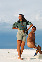 Surprised naked man putting on clothes while a woman poses for the camera in the desert