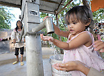 A girl enjoys clean water just as it comes from the pump in the Cambodian village of Pheakdei.
