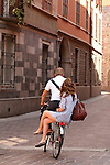 A couple rides a bike through Como, Italy on Lake Como with the girl sitting on the back of the bike
